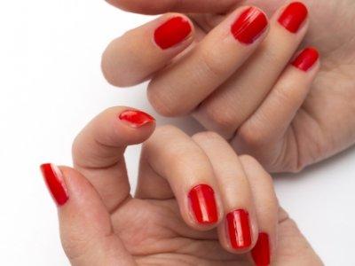 赤いマニキュアの女性の手